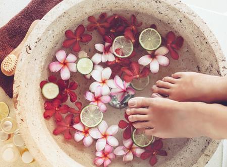 pedicura: Baño de pies en un recipiente con cal y flores tropicales, tratamiento de pedicura spa, vista desde arriba