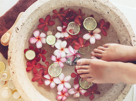 Foot bath in bowl with lime and tropical flowers, spa pedicure treatment, top view 免版税图像