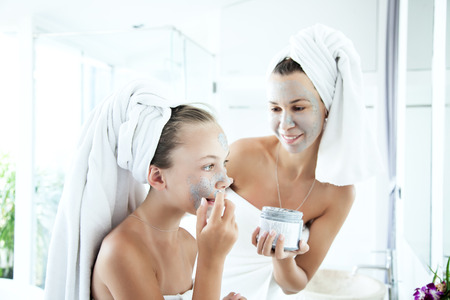 tween: Mother and tween daughter make a clay facial mask, family scin care in the bathroom