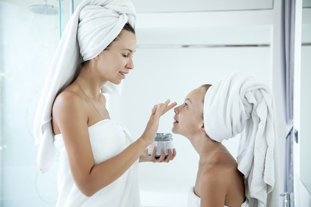modern girls: Mother and tween daughter make a clay facial mask, family scin care in the bathroom