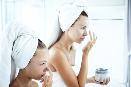 clays: Mother and tween daughter make a clay facial mask, family scin care in the bathroom