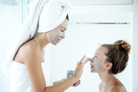 daughter mother: Mother and tween daughter make a clay facial mask, family scin care in the bathroom