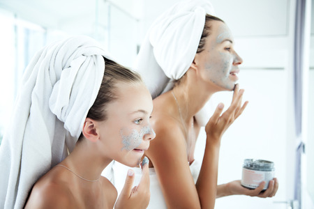 Mother and tween daughter make a clay facial mask, family scin care in the bathroom