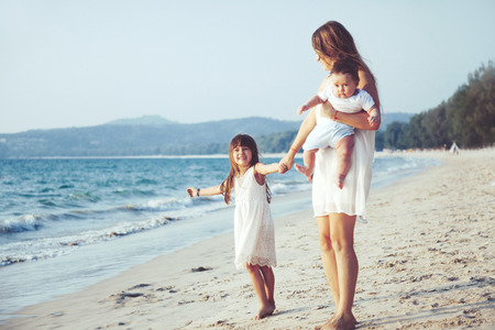 childen: Family walking on the evening beach during sunset. Two childen with mom. Stock Photo