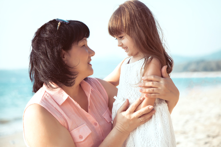 grandmother: Grandmother and granddaughter standing in over sea Stock Photo