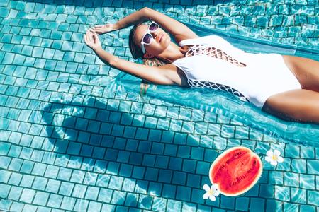 Mädchen schwimmt auf Strandmatratze und Wassermelone in den blauen Pool zu essen. Tropische Früchte Ernährung. Sommerurlaub idyllisch. Draufsicht. Lizenzfreie Bilder