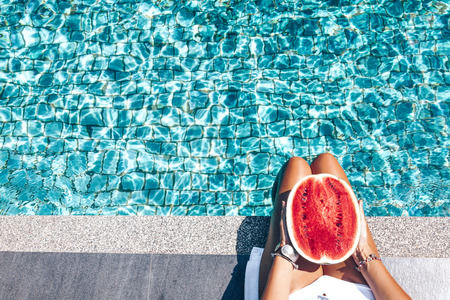 Girl holding watermelon in the blue pool, slim legs.