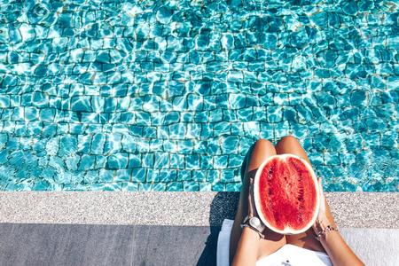Menina, segurando melancia na piscina azul, pernas finas.