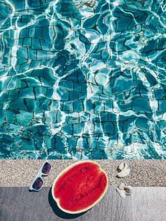 Watermeloen, zonnebril en spa bloemen in de buurt van het blauwe zwembad. Tropisch fruit dieet. Zomervakantie idyllisch. Stockfoto