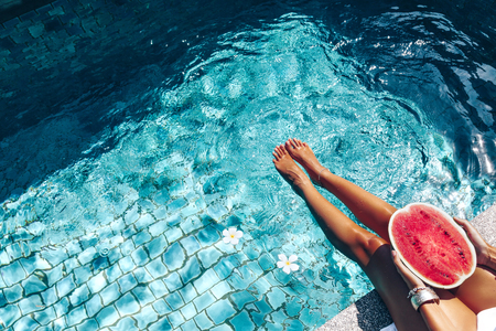 Girl holding watermelon in the blue pool, slim legs.