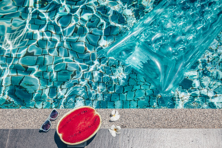 matress: Watermelon, sunglasses and floating matress the blue pool. Tropical fruit diet. Summer holiday idyllic.