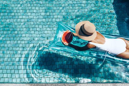 Menina que flutua no colchão da praia e que come a melancia na associação azul. Dieta de frutas tropicais. Férias de verão idílica. Vista do topo.