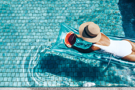 frutas divertidas: Muchacha que flota en el colchón de la playa y comer sandía en la piscina azul. dieta de la fruta tropical. vacaciones de verano idílico. Vista superior.