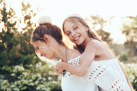 9 10 years: Tween daughter hugging with her mom in summer sunlight