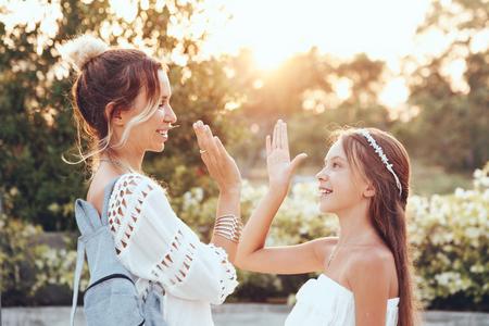 tween: Tween daughter holding hands her mom in summer sunlight Stock Photo