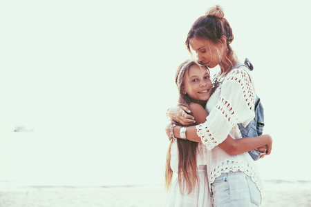 9 10 years: Tween daughter hugging with her mom, boho oriental style Stock Photo