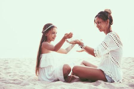 Tween dochter en haar moeder spelen met zand op het strand, boho oosterse stijl