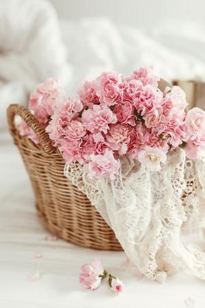 Estilo elegante lamentable. flores en colores pastel de color rosa en la cesta de mimbre en la cama. Foto de archivo - 54741236
