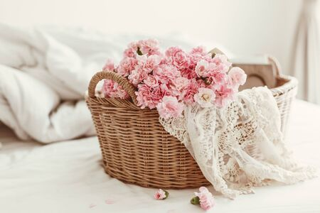 Shabby chic stijl. Roze pastel bloemen in de rieten mand op het bed.