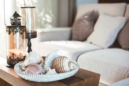 Decoração interior de praia: conchas marinhas e lanternas na mesa de café de madeira, cores naturais. Detalhe da sala de estar. Banco de Imagens