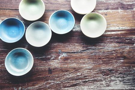 ceramica: platos de cerámica hechos a mano en una mesa de época antigua, vista desde arriba Foto de archivo