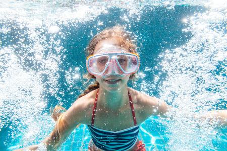 9 年古い子供の身に着けているマスク スイミング プールでダイビング撮影水中