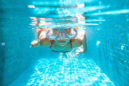 9 10 years: 9 years old child wearing diving mask swimming in the pool, underwater shot
