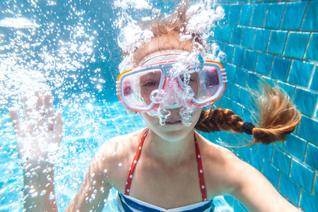 pool preteen: 9 years old child wearing diving mask swimming in the pool, underwater shot