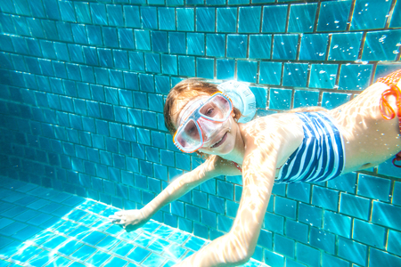 preteens beach: 9 years old child wearing diving mask swimming in the pool, underwater shot