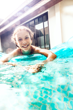 matress: 9 years old child swimming on the inflatable matress in the pool at the back yard of villa resort, split underwater shot in sunlight Stock Photo