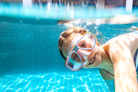 preteens girl: 9 years old child wearing diving mask swimming in the pool, underwater shot