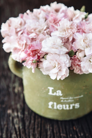 chic: Shabby chic flowers in clay pot on rustic wooden background