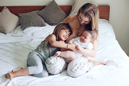 baby 4 5 years: Young mom with her 5 years old dauhter and 4 months old baby dressed in pajamas are relaxing and playing in the bed at the weekend together, lazy morning