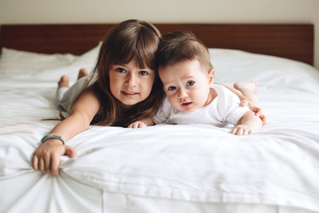 siblings: Siblings hugging and laying down on the bed in bedroom