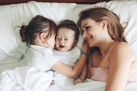Mamã nova com os seus 5 anos de idade dauhter e 4 meses de idade do bebê de pijama são relaxantes e jogar na cama no fim de semana juntos, manhã preguiçosa