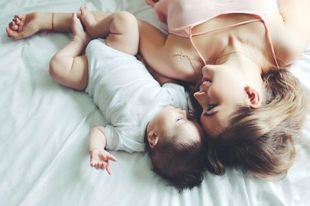 嬰兒: 美麗的縱向媽媽在臥室與她4個月玩大的嬰兒,頂視圖