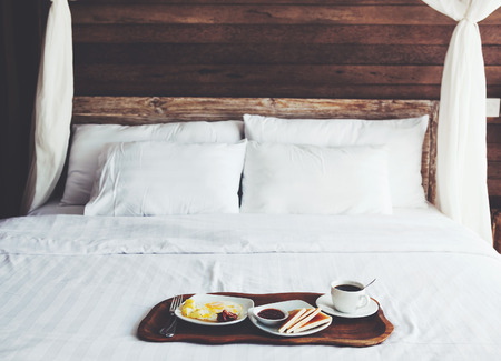 white linen: Brekfast on a tray in bed in hotel, white linen, wooden intreior Stock Photo