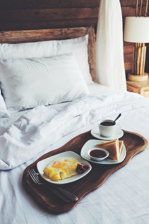 hotel bed: Brekfast on a tray in bed in hotel, white linen, wooden intreior Stock Photo