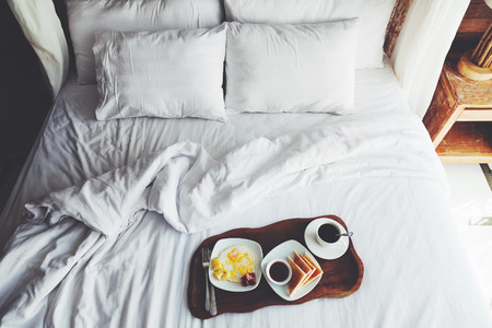 Brekfast on a tray in bed in hotel, white linen, wooden intreior Фото со стока