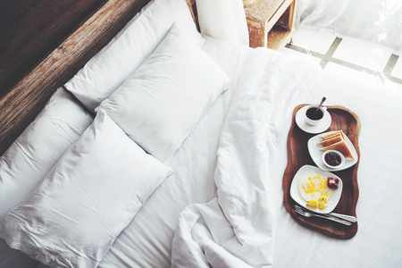 Brekfast on a tray in bed in hotel, white linen, wooden intreior Stockfoto