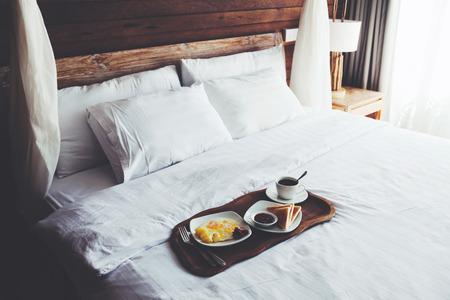 Brekfast trên một cái khay trên giường trong khách sạn, vải lanh trắng, intreior gỗ