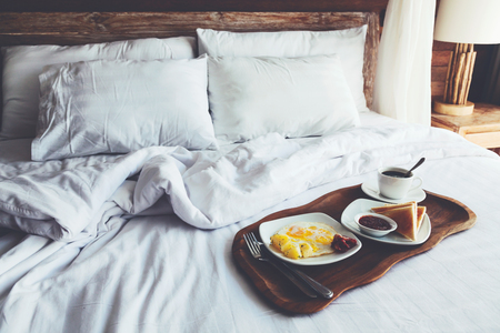 Brekfast on a tray in bed in hotel, white linen, wooden intreior Standard-Bild
