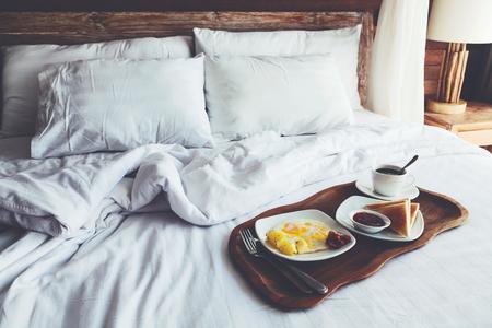 Colazione a buffet su un vassoio a letto in hotel, lino bianco, interno in legno Archivio Fotografico