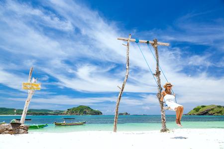 Mujer con vestido blanco y sombrero de balanceo en la playa tropical, día soleado, buen tiempo Foto de archivo
