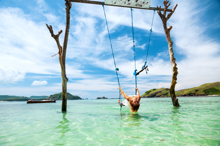 paradise beach: Woman swinging at tropical beach, sunny day, good weather. Swinging in paradise island.