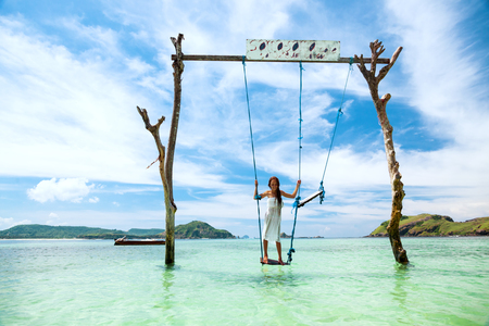 indonesia: Girl swinging at tropical beach, sunny day, good weather. Swinging in paradise island.