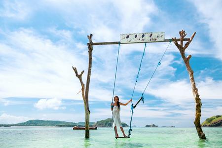 island paradise: Girl swinging at tropical beach, sunny day, good weather. Swinging in paradise island.
