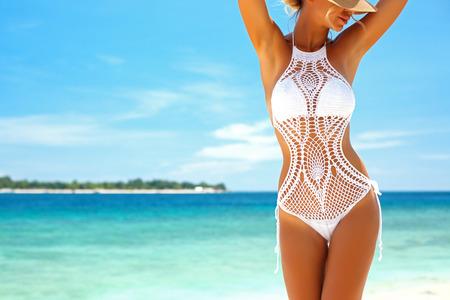 Mulher bonita que desgasta o biquini de crochê que levantam sobre a vista do mar, estilo de vida de praia