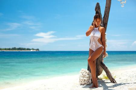 Hermosa mujer vistiendo bikini de ganchillo que presentan sobre la vista al mar, el estilo de vida de playa
