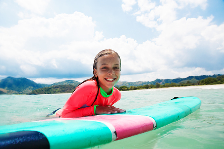 recreational: Kid girl is learning surfing Stock Photo